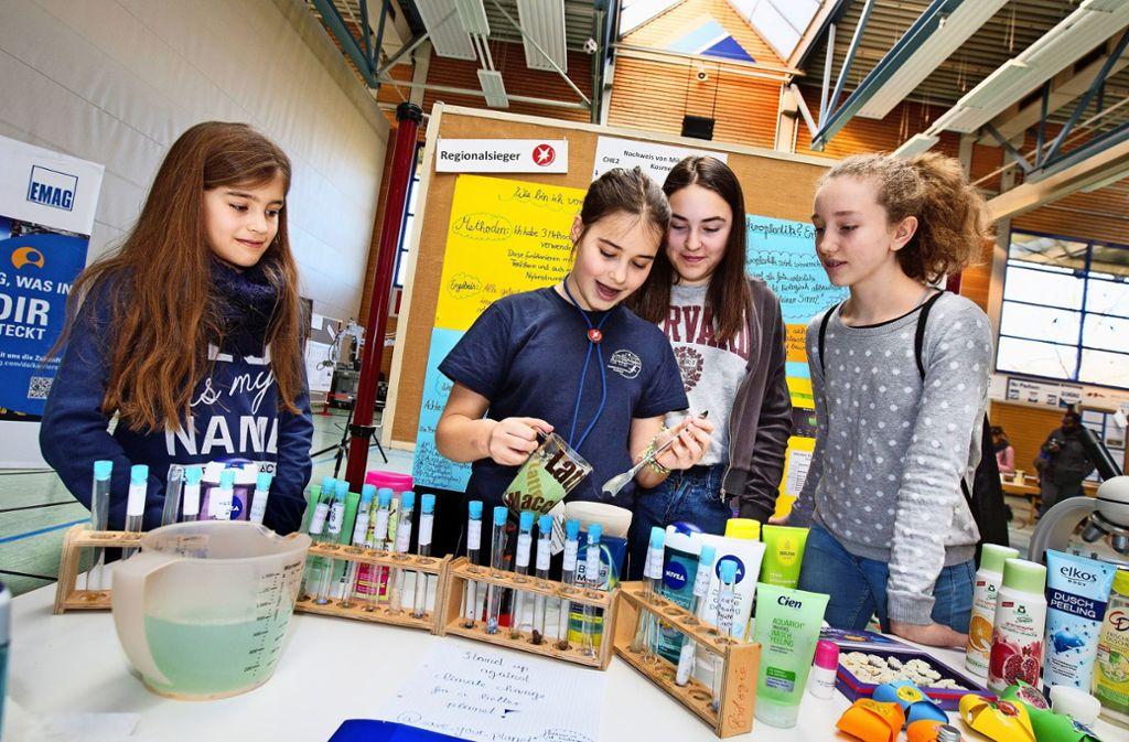 Joy Anders aus Süßen (Zweite von links) demonstriert drei jungen Besucherinnen, wie sie kosmetische Produkte auf winzige Plastikbestandteile untersucht hat. Foto: Horst Rudel