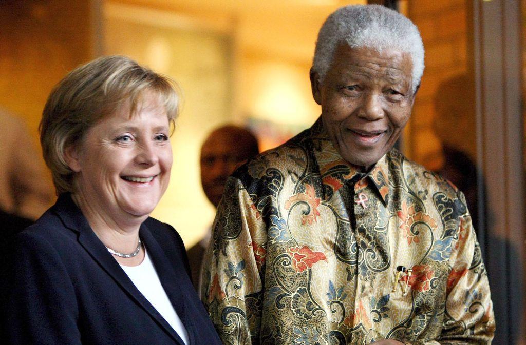 Auf den populären Freiheitskämpfer und späteren Präsidenten Nelson Mandela (1918-2013) trifft Bundeskanzlerin Angela Merkel im Oktober 2007 in Johannesburg. Foto: dpa