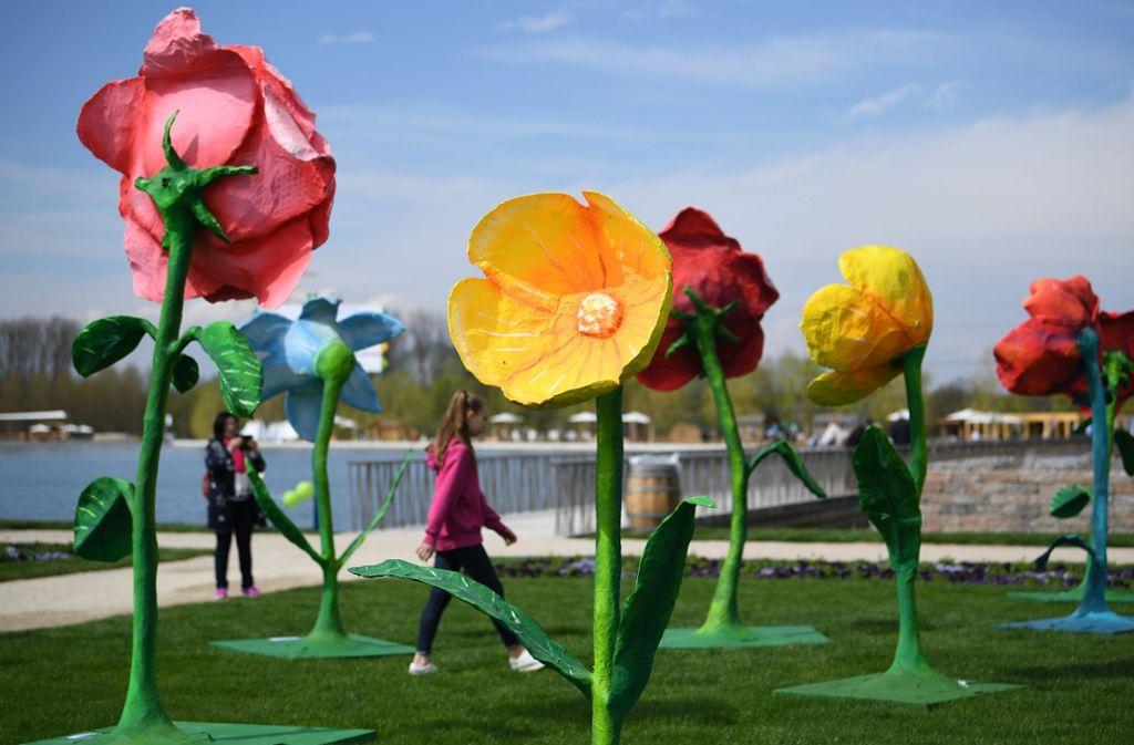 Besucher laufen bei der Eröffnung der diesjährigen Landesgartenschau in Lahr an überdimensionalen Blumen vorbei. Foto: dpa