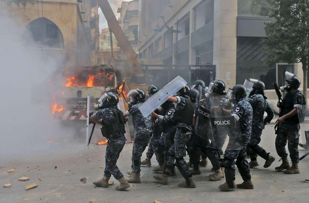Die Polizei bahnt sich mit Schutzschildern ihren Weg. Foto: AFP/STR