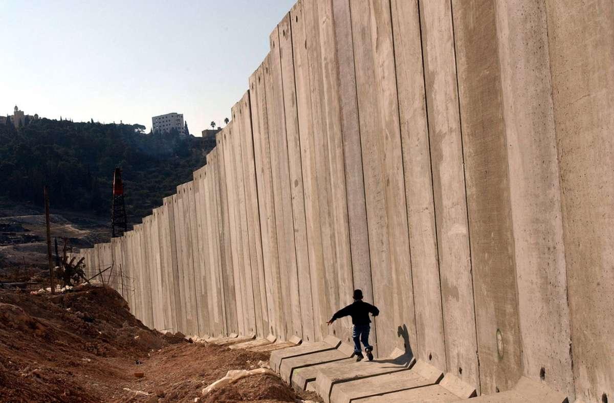 Ein palästinensisches Kind spielt vor der israelischen Grenzmauer in Ostjerusalem. Weitere interessante Neuerscheinungen finden Sie in unserer Bildergalerie. Foto: picture alliance/dpa