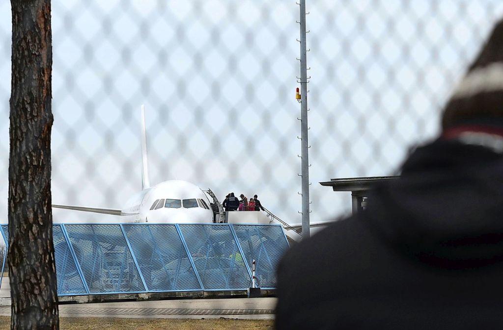 Abgelehnte Asylbewerber steigen im Baden Airport in ein Flugzeug, das sie in ihre Herkunftsländer zurückbringt. Dabei werden sie von Polizisten begleitet. Foto: dpa