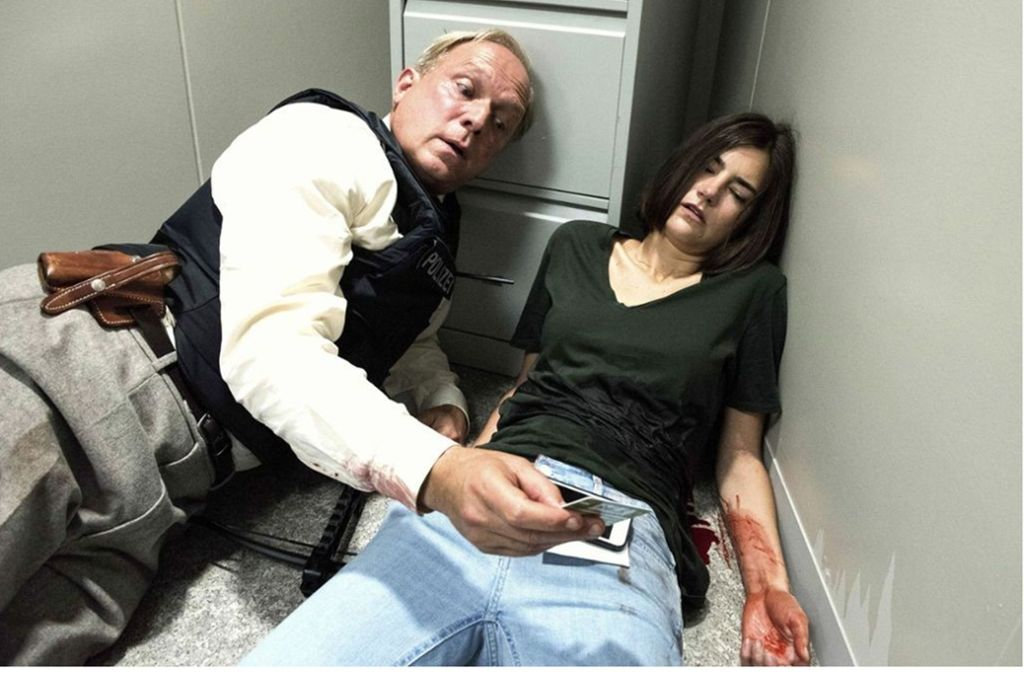 Murot (Ulrich Tukur) checkt den Ausweis der verletzten Geiselnehmerin Eschenbach (Nadine Dubois). Foto: HR/Bettina Müller