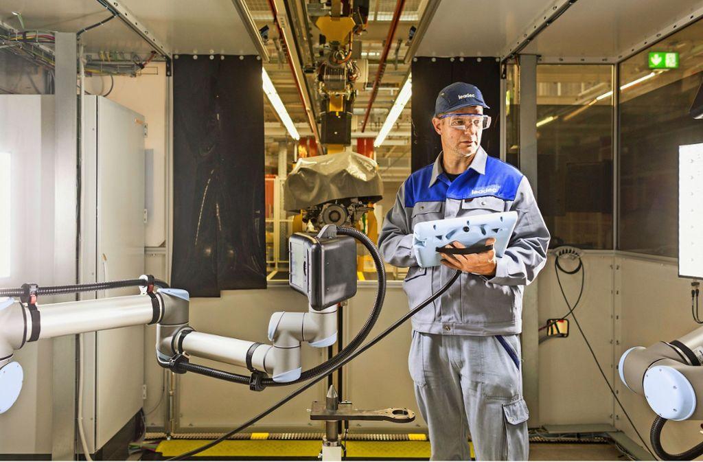 Ein Leadec-Mitarbeiter ist mit Wartungs- und Reinigungsarbeiten in einer Lackieranlage in einem Motorenwerk eines Automobilkunden tätig. Foto: Leadec