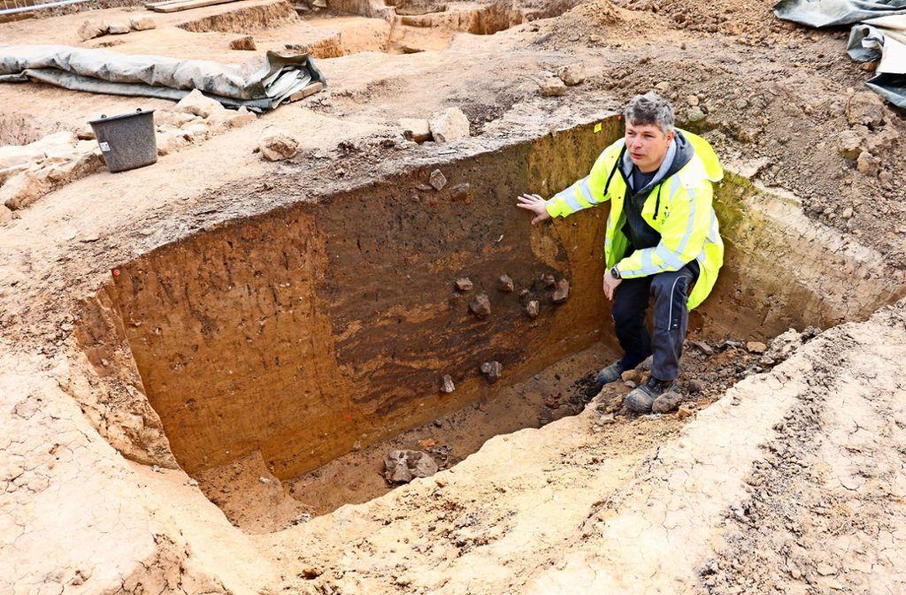 Der Archäologe Sascha Schmidt zeigt  die sackförmige Vorratsgrube, den an  dieser Stelle bislang ältesten Fund. Foto: Marta Popowska
