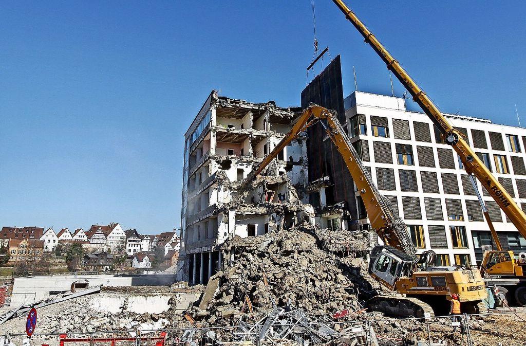 Ein Schutzvorhang, der an dem rechten Kran hängt,  sorgt dafür, dass beim Abbruch des Rathaus-Altbaus keine Bruchstücke das neue Gebäude beschädigen. Foto: factum/Bach
