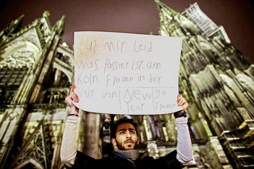 Dieser Mann vor dem Kölner Dom schämt sich für seine Geschlechtsgenossen. Foto: dpa