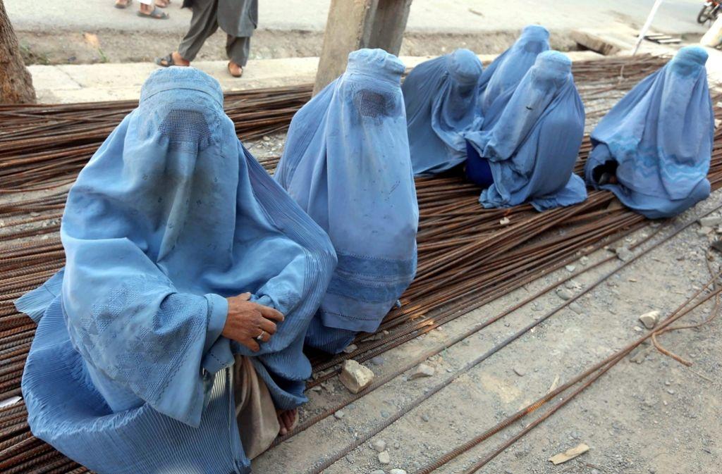 Mit einer Burka bekleidete Frauen warten in Afghanistan auf der Straße (Symbolfoto). Foto: dpa
