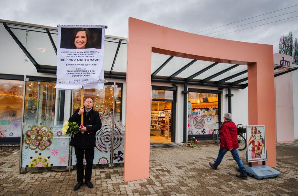 Ein Mann bringt mit einem Schild seinen Unmut über die aktuelle Politik vor dem Drogeriemarkt in Kandel (Rheinland-Pfalz) zum Ausdruck. In dem Laden wurde am Mittwoch ein junges Mädchen von ihrem afghanischen Ex-Freund erstochen. Foto: dpa