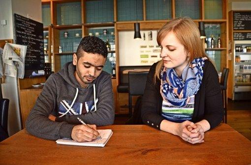 """Mohamad Bashar Alajloub schreibt für mich einige Sätze auf Arabisch.  """"Du hörst dich an, wie wenn ein Kurde Arabisch spricht"""", meint er zu meinem Sprachtalent. Foto: Paula Brendel"""