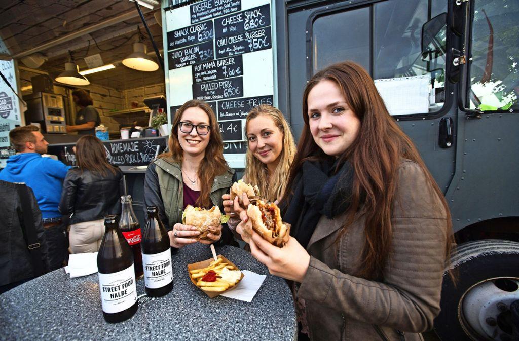 Diese drei Frauen lassen sich Burger, Street Food Bier und Cola schmecken. Foto: Ines Rudel