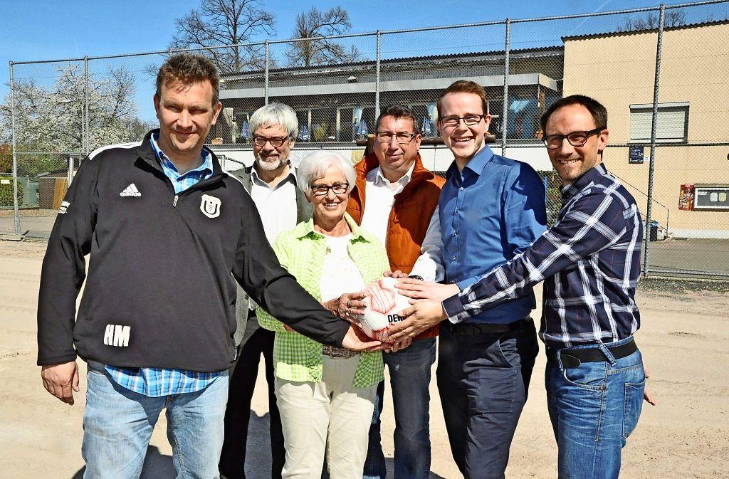 Hilmar Maier (links), der Vorsitzende der SG 07 Untertürkheim, freut sich mit anderen Beteiligten darüber, dass auf dem Kunstrasenplatz bald wieder ordentlich Fußball gespielt werden kann Foto: Georg Linsenmann