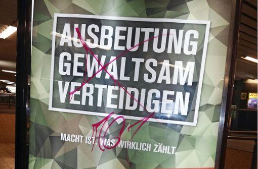 Aktivisten hängen militärkritische Plakate auf