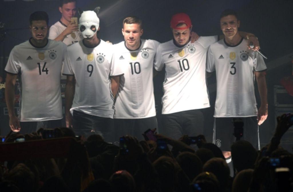 Die Fußballnationalspieler Emre Can (links), Lukas Podolski (Mitte) und Jonas Hector (rechts) posieren mit Rapper Cro in den neuen Leibchen. Foto: dpa