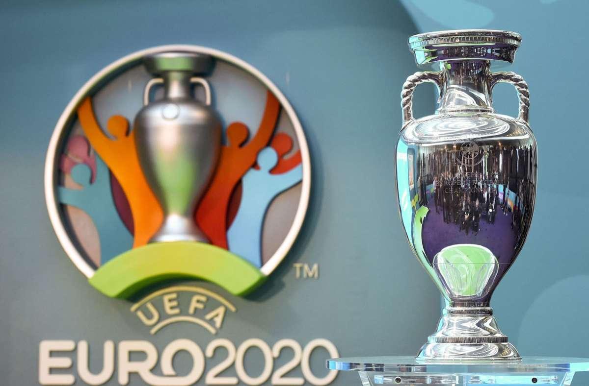 Der EM-Pokal neben dem Logo für die UEFA EURO 2020. (Symbolbild) Foto: dpa/Facundo Arrizabalaga