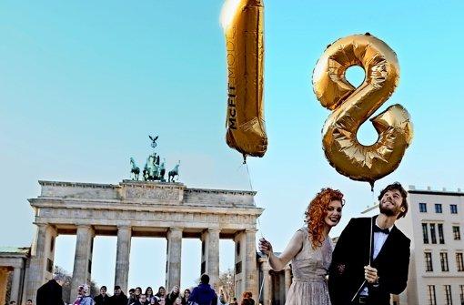 Zwei Models werben vor dem Brandenburger Tor für die 18. Fashion Week. Foto: dpa