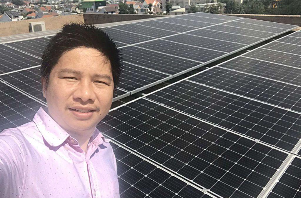 Thuong Duong, der Ecoligo-Vertreter in Vietnam, vor einer Solaranlage auf einem Firmendach. Foto: Ecoligo