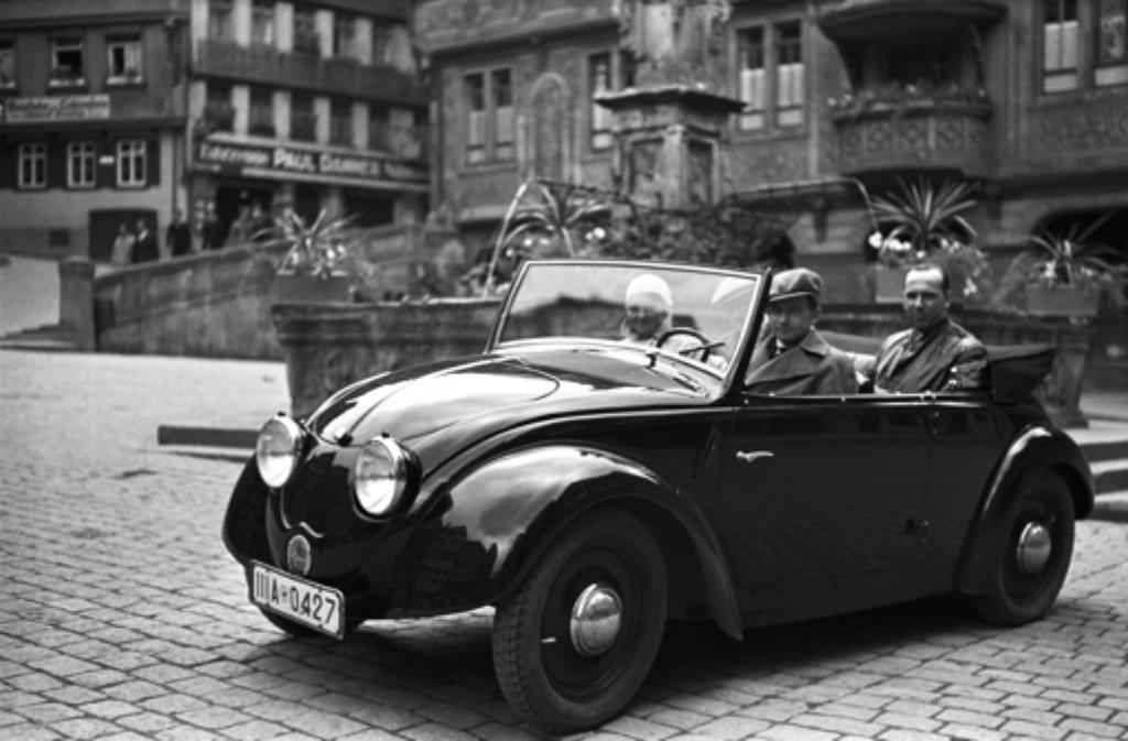 Das Werksfoto aus dem Jahr 1936 zeigt Ferry Porsche am Steuer des zweiten Volkswagen-Prototypen (V2), fotografiert auf dem Marktplatz in Tübingen. Neben ihm seine Frau Dorothea. Auf dem Rücksitz Hellmuth Zarges, ein Freund der Familie Porsche. Foto: Porsche Werksfoto/dpa