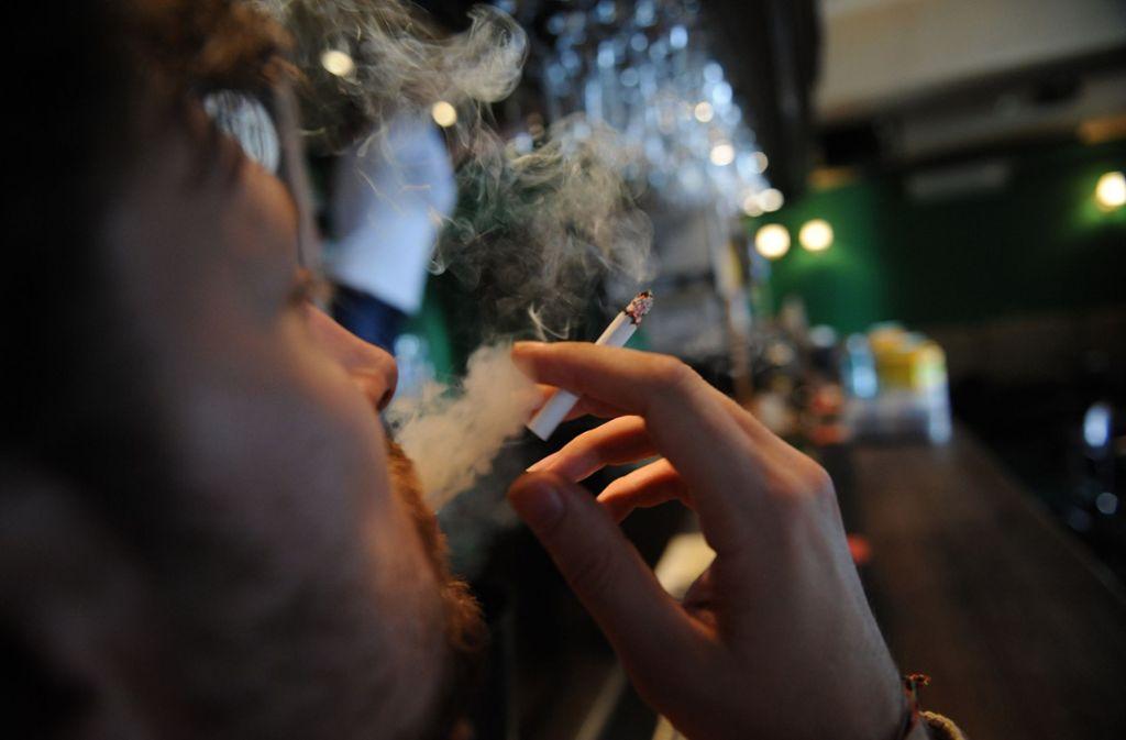 Ein Raucher an einer Bar. Das soll es in Baden-Württemberg bald nicht mehr geben, wenn der Gesundheitsminister seine Pläne durchsetzt. (Symbolfoto) Foto: AFP