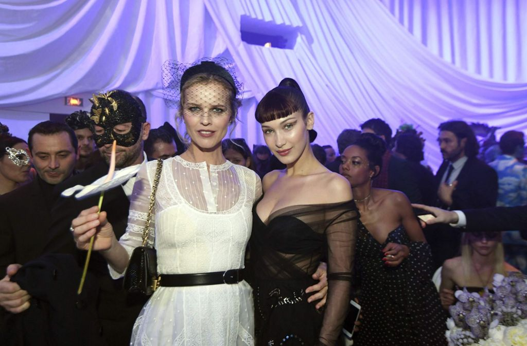 Dior überzeugte in der Fashion Show in Paris mit auffälligen Masken. Nach dem Laufstegevent feierten Gäste wie Eva Herzigova (links) und Bella Hadid. Foto: AFP