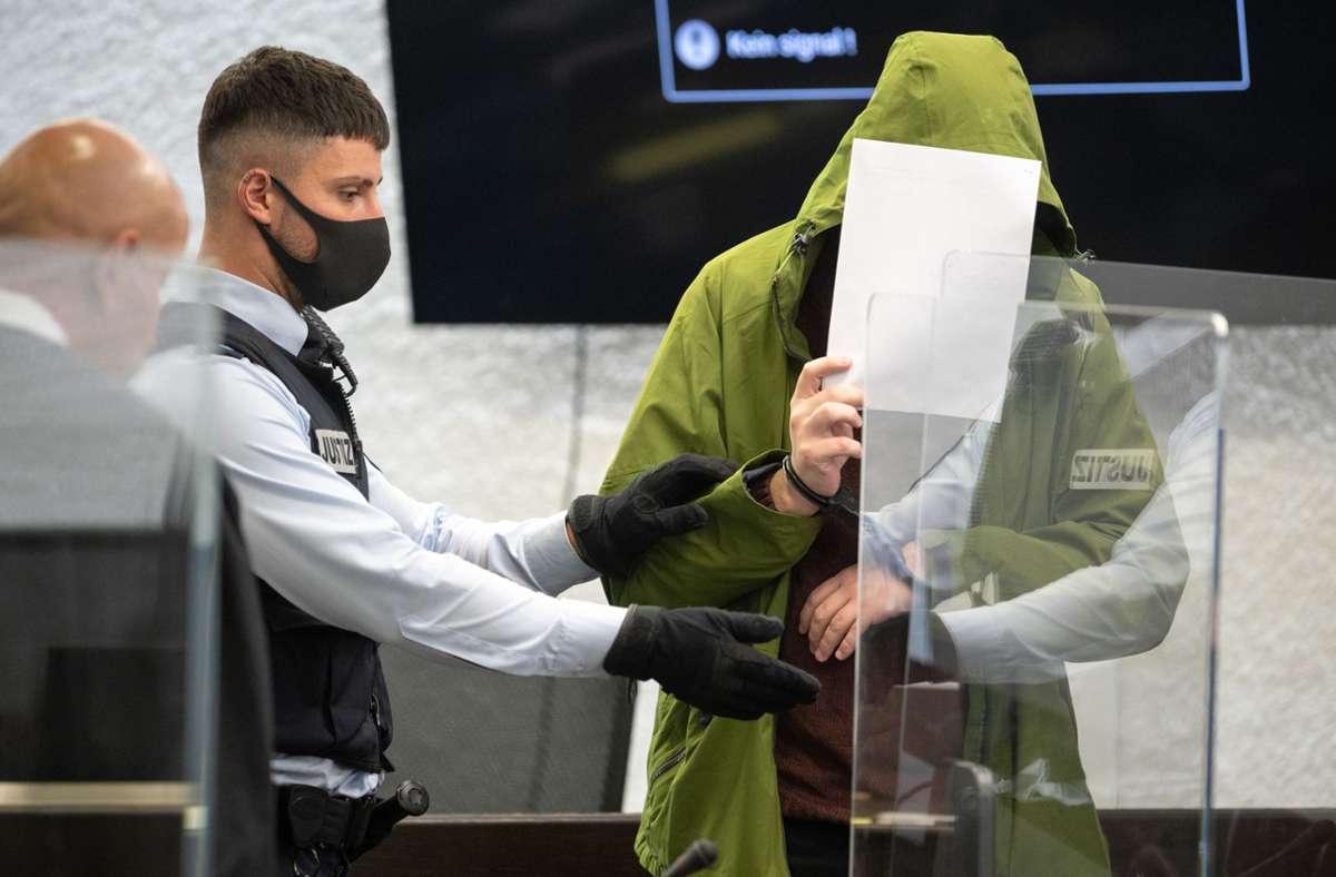 Der Täter verdeckt am Landgericht Stuttgart sein Gesicht. Foto: dpa//Sebastian Gollnow