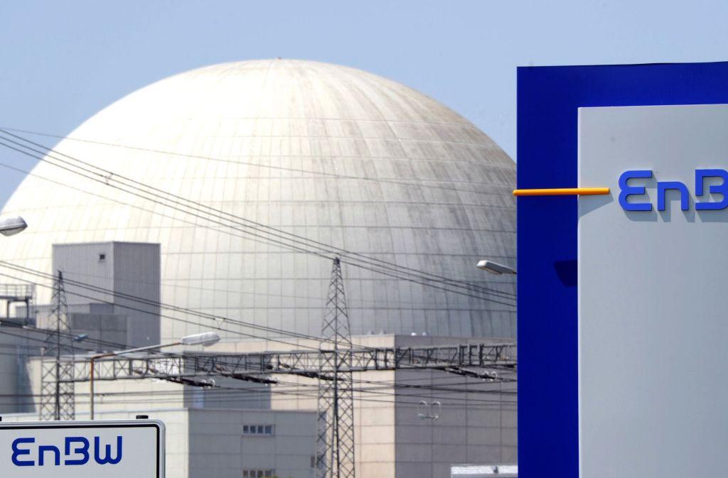 Hinter einem EnBW Logo ist das Kernkraftwerk Philippsburg  zu sehen Foto: dpa