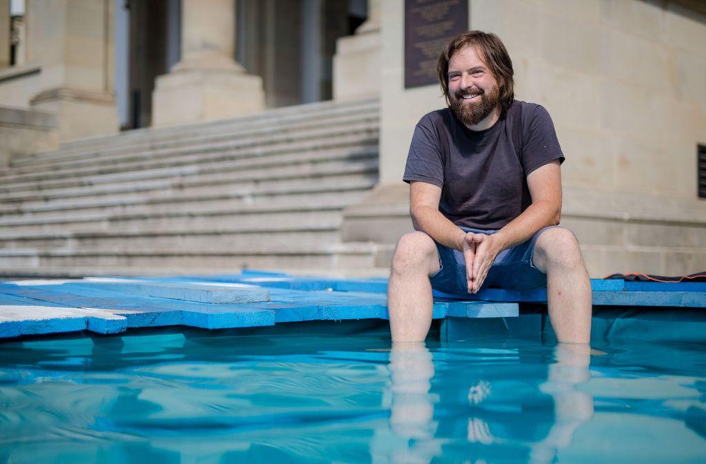 Der Architekt Peter Weigand badet seine Füße im Becken am Stadtpalais. Foto: Lichtgut/Christoph Schmidt
