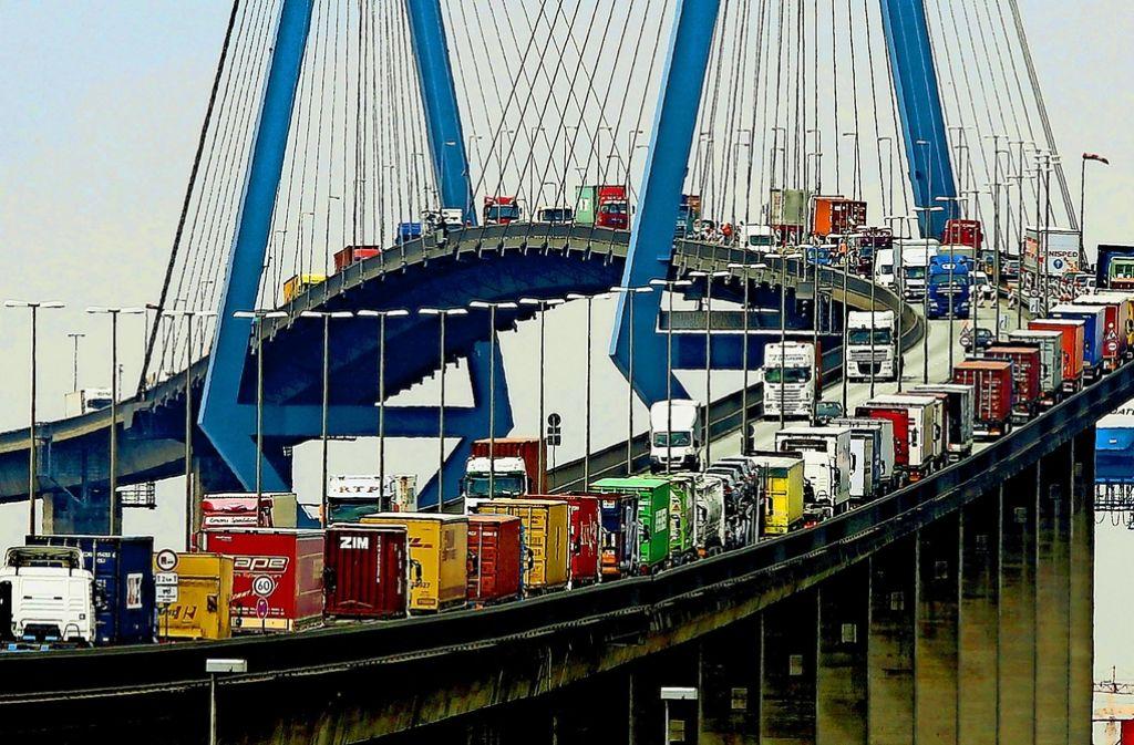 Mit Containern beladene Lastwagen stauen sich auf der Köhlbrandbrücke im Hafen von Hamburg: Mehr als ein Jahrzehnt lang hat fast die gesamte Lastwagenbranche ihre Kunden in Europa durch illegale Absprachen geschröpft. Foto: dpa