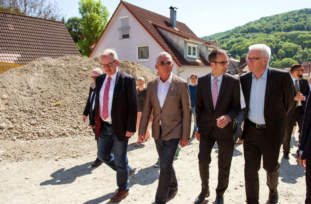 Der Erste Landesbeamte Michael Knaus, Innenminister Thomas Strobl (CDU), Bürgermeister Frank Harsch sowie Ministerpräsident Winfried Kretschmann (Grüne) in Braunsbach. Foto: dpa