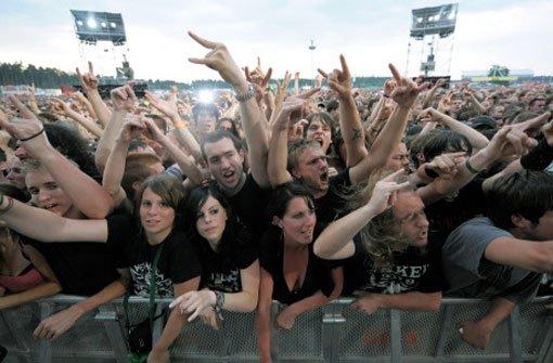 Fans jubeln am 4. Juli 2009 während eines Auftritts der US-Gruppe Metallica beim Open-Air-Konzert auf dem Hockenheimring. Der Hockenheimring soll im August 2013 ein großes Open-Air-Festival bekommen. Foto: dpa