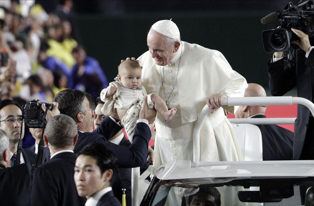 Papst Franziskus war zu Besuch in Japan, auf dem Weg zur Messe streichelte er Kindern über den Kopf, die zu ihm gehalten wurden. Foto: dpa/Gregorio Borgia