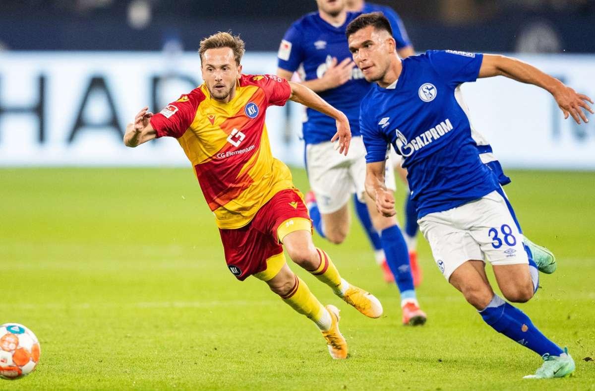 Lucas Cueto von Karlsruhe und Schalkes Mehmet Can Aydin verfolgen den Ball. Foto: dpa/Marcel Kusch