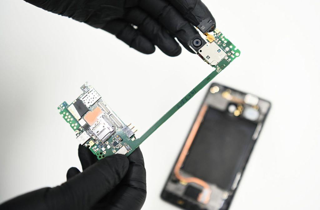 Ein IT-Forensiker zeigt die Hauptplatine eines Smartphones. Foto: dpa/Nicolas Armer