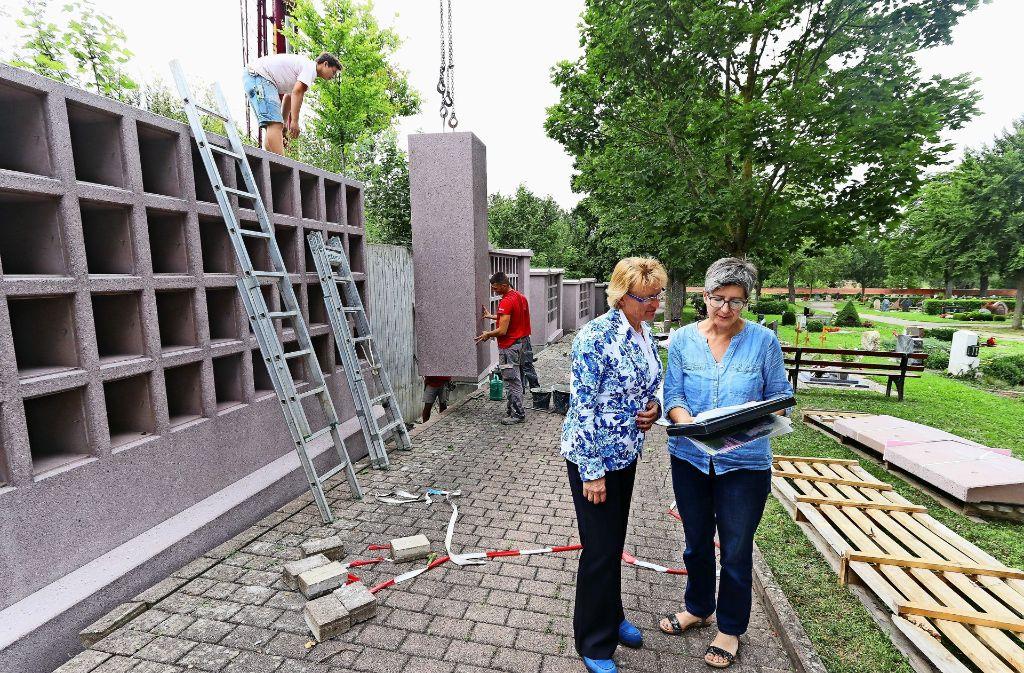 Susanne Widmaier und Margit Dürr (von links) sind dabei, als die neuen Urnenwände aufgestellt werden. Foto: factum/Granville