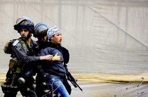 Israelische Polizisten stoppen einen palästinensischen Demonstranten. Foto: AFP
