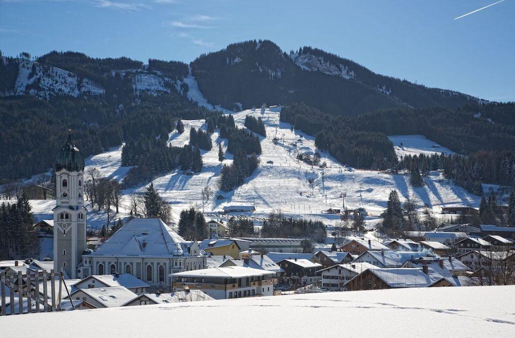 Winterliches Nesselwang mit der Hausberg Alpspitze, dem Skigebiet und der Pfarrkirche im Hintergrund. Foto: Quelle /Rechte Nesselwang Marketing GmbH