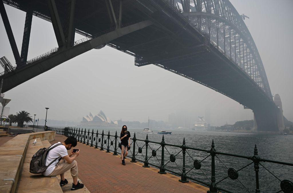 Die Wahrzeichen von Sydney, das Opernhaus und die Harbour Bridge, sind im Dunst kaum mehr zu erkennen. Foto: AFP/PETER PARKS