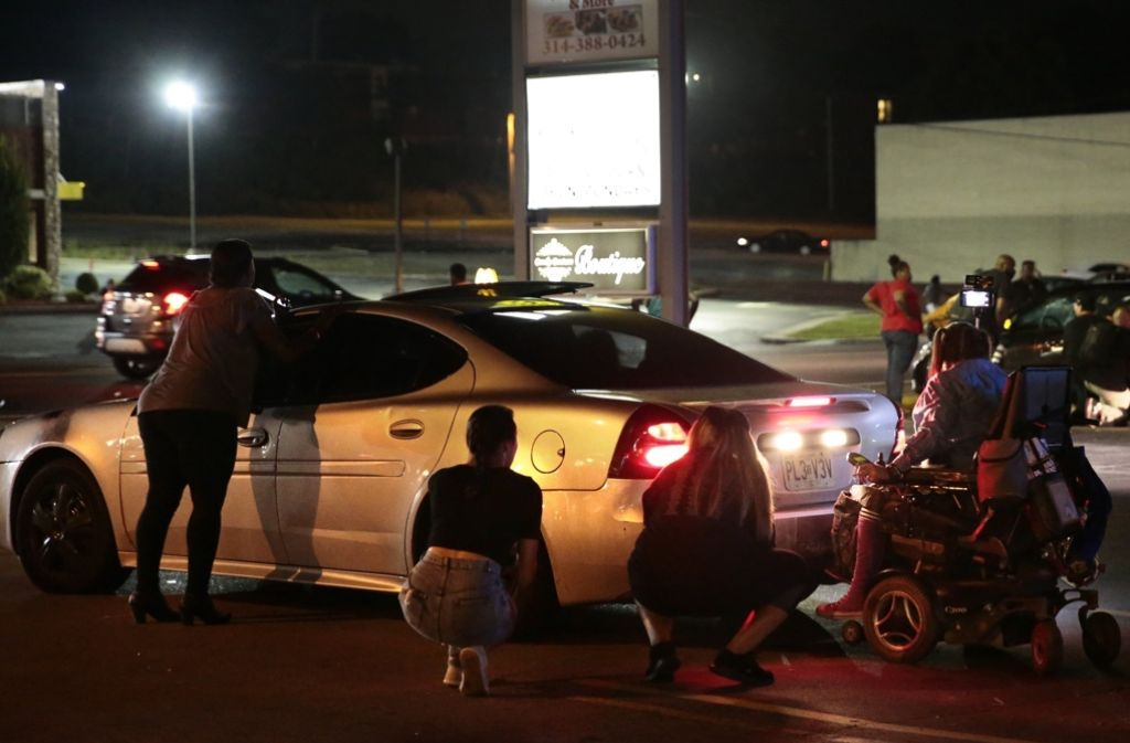 Demonstranten verstecken sich in Ferguson hinter Autos. Foto: AP/St. Louis Post-Dispatch