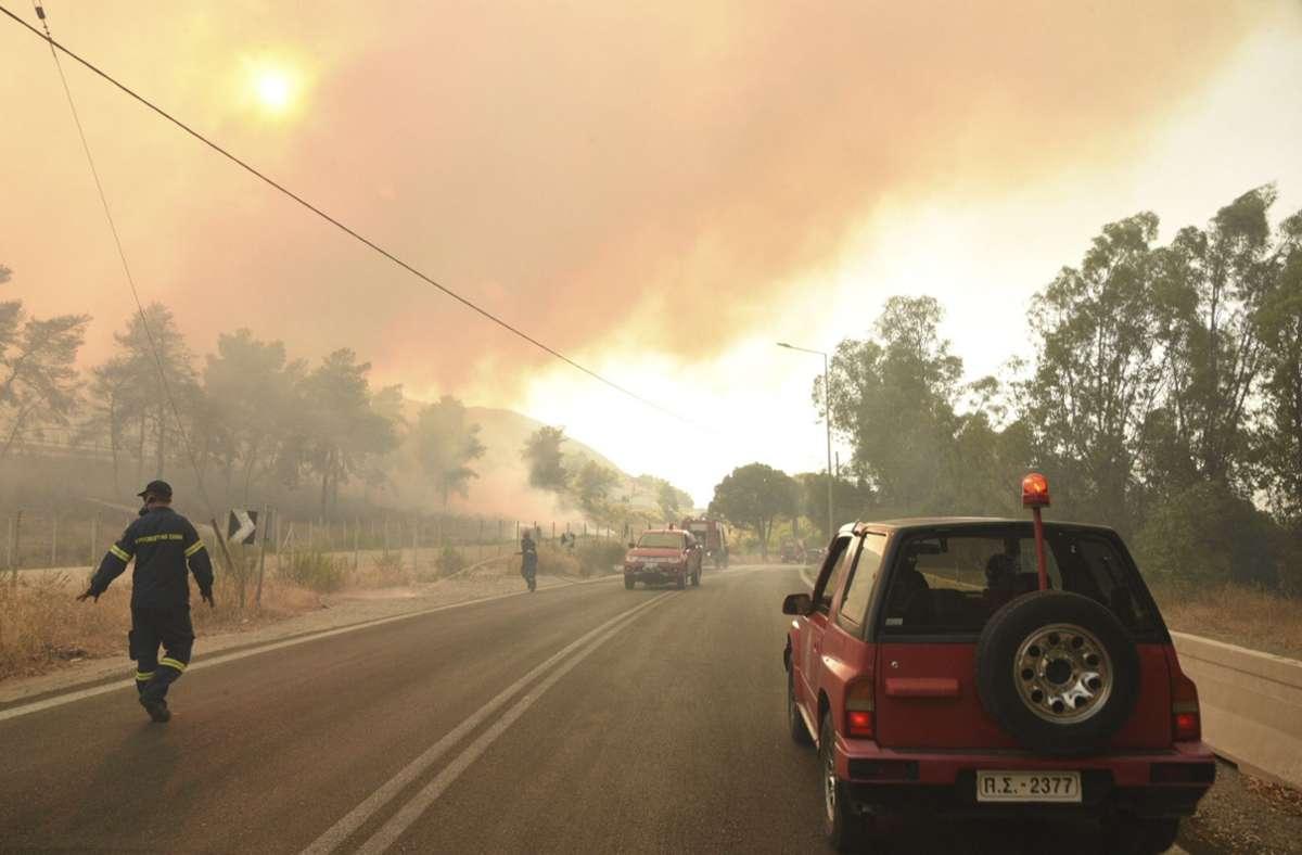 Feuerwehrleute bekämpfen einen Waldbrand in der Nähe des Dorfes Lampiri, gefährlich nah zu den Küstenstädten. Foto: AP/dpa/Andreas Alexopoulos