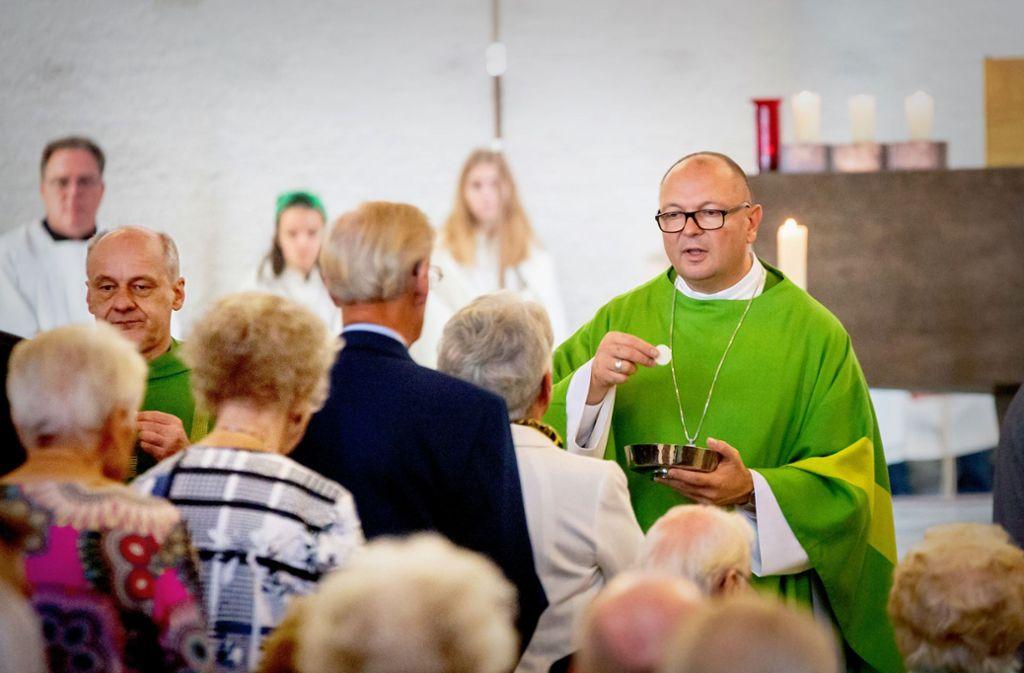 Weihbischof  Gerhard Schneider (re.)  beim Heiligen Abendmahl. Foto: Lichtgut/Julian Rettig