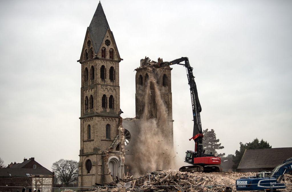 Ein Abrissbagger zerstört am 9. Januar 2018 in Erkelenz-Immerath (Nordrhein-Westfalen) einen Turm des Immerather Doms. Das frühere Gotteshaus der katholischen Pfarrei St. Lambertus war seit 2013 entwidmet und damit kein Gotteshaus mehr. Der Ort Immerath muss dem nahenden Braunkohletagebau Garzweiler weichen. Foto: dpa