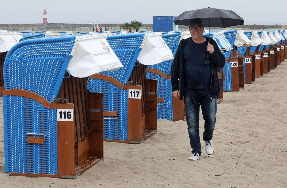 Regenschirm statt Badehose und leere Strandkörbe: So sieht es gerade in Warnemünde aus Foto: dpa/Bernd Wüstneck