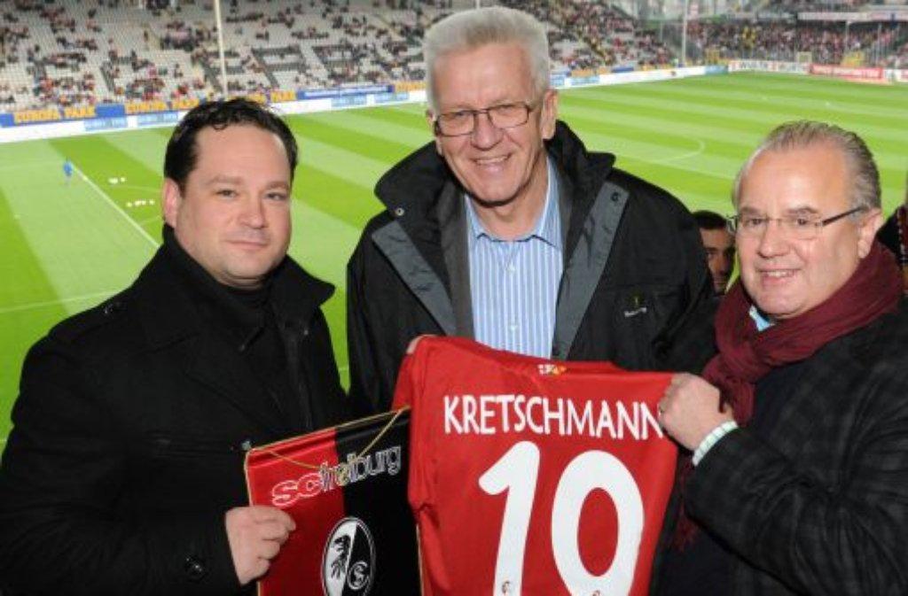 Lassen Sie sich nicht täuschen vom Kretschmann-Trikot des SC Freiburg, das der amtierende Ministerpräsident von Baden-Württemberg von den Breisgauern beim Derby zwischen Freiburg und dem VfB geschenkt bekam. Tief im Herzen ist Winfried Kretschmann (Mitte) natürlich ein VfB-Fan: Ich bin seit schätzungsweise zehn Jahren Mitglied beim VfB, in meiner Familie sind sie durch und durch VfB-Fans. Auch einer seiner Vorgänger ... Foto: dpa