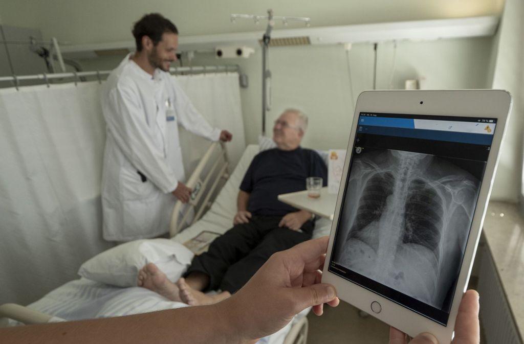 Oberarzt Michael Svoboda bei einem seiner Patienten. Röntgenbilder  kann er nun  direkt am Bett  auf dem Tablet zeigen. Foto: factum/Weise