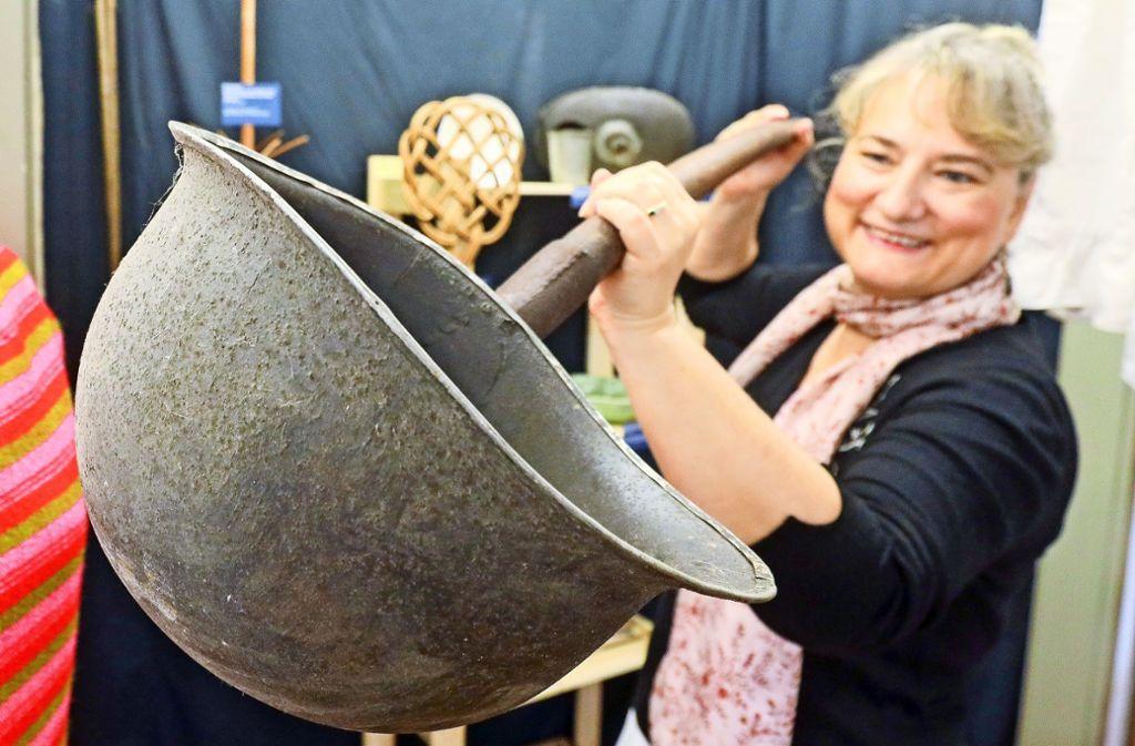 Sabine Rathgeb zeigt einen Gülleschöpfer, hergestellt aus einem Stahlhelm.  Im Heimatmuseum geht es um Kunststoff – und wie die Menschen einst ohne lebten. Foto: factum/Simon Granville