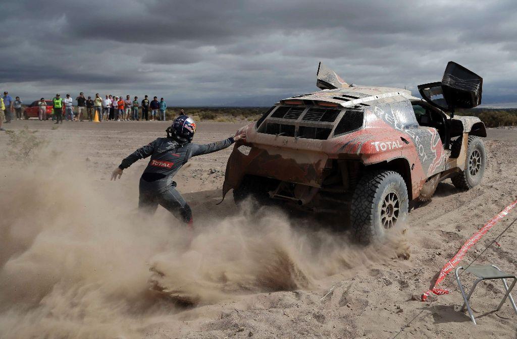 Peugeot-Fahrer Cyril Despres schiebt sein Auto an. Die Rallye Dakar ist brandgefährlich – und sie produziert spektakuläre Bilder. Eine Auswahl der Rallye 2016 zeigen wir in der folgenden Fotostrecke. Foto: AP