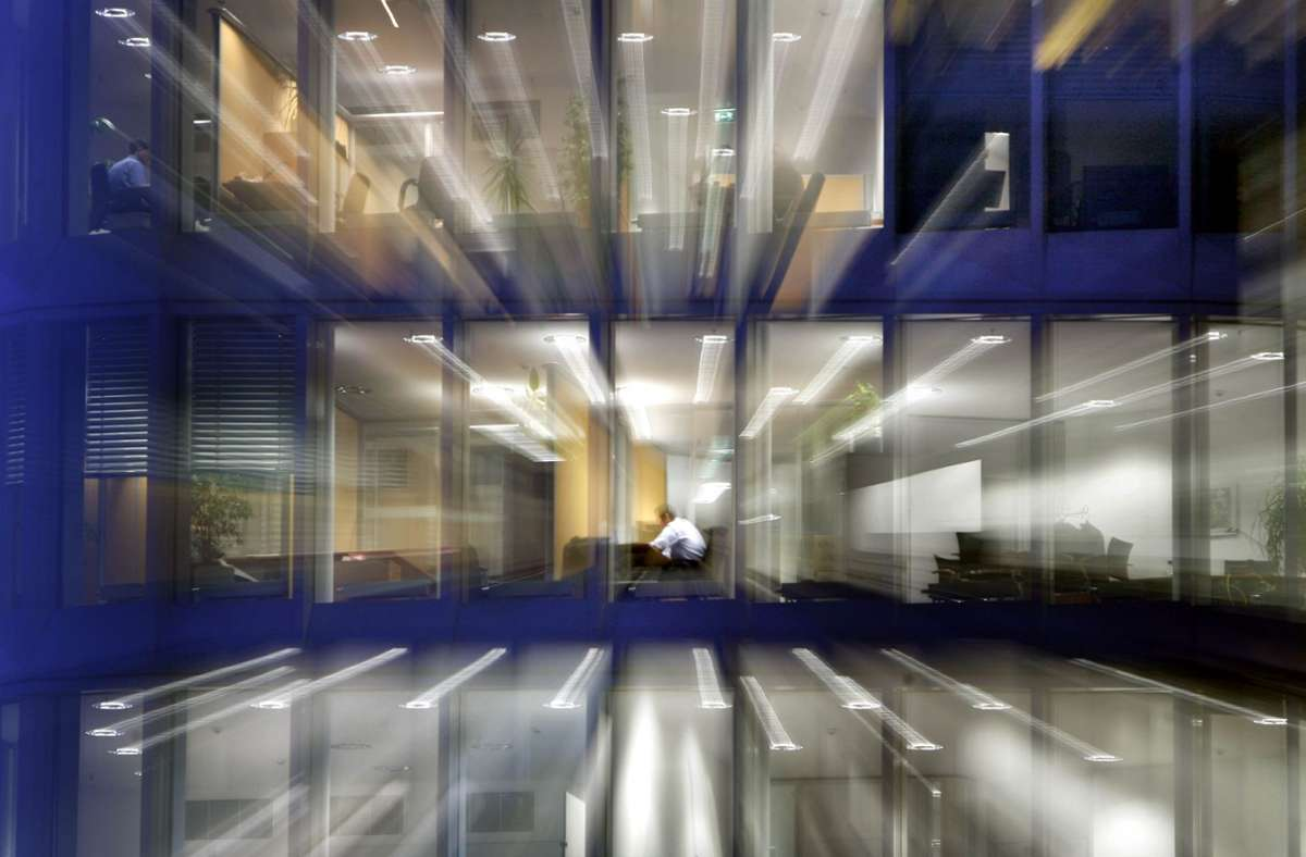 Nach Einbruch der Dunkelheit sitzt ein Angestellter in seinem Büro am Schreibtisch. Foto: dpa/picture alliance