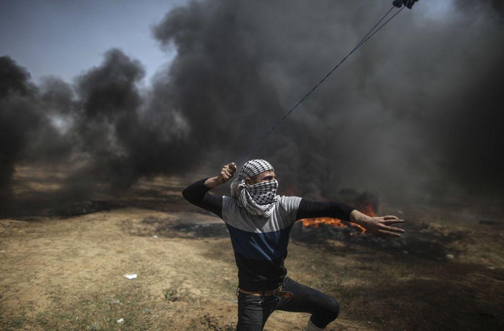 Ein Palästinenser schleudert bei Zusammenstößen zwischen palästinensischen Demonstranten und israelischen Soldaten im Gazastreifen Steine mit einer Schleuder. Foto: dpa