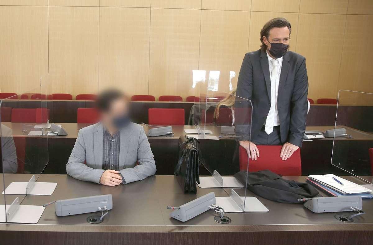 Der angeklagte Arzt sitzt mit Maske im Gerichtssaal neben Verteidiger Rechtsanwalt Michael Noll vor seinem Prozess in Düsseldorf. Foto: dpa/David Young