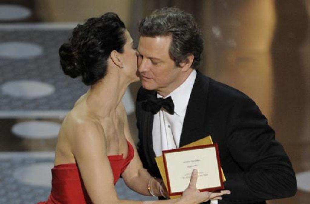 Colin Firth bekommt von Sandra Bullock den Oscar für den besten männlichen Schauspieler überreicht - und ein Küsschen dazu. Foto: dapd
